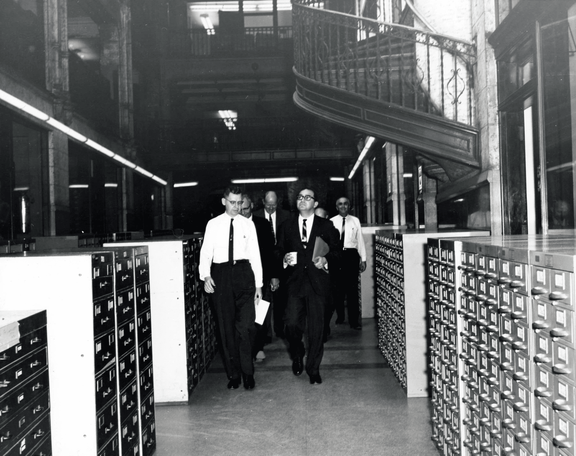 vintage black and white photograph of a group of men walking through grove arcade