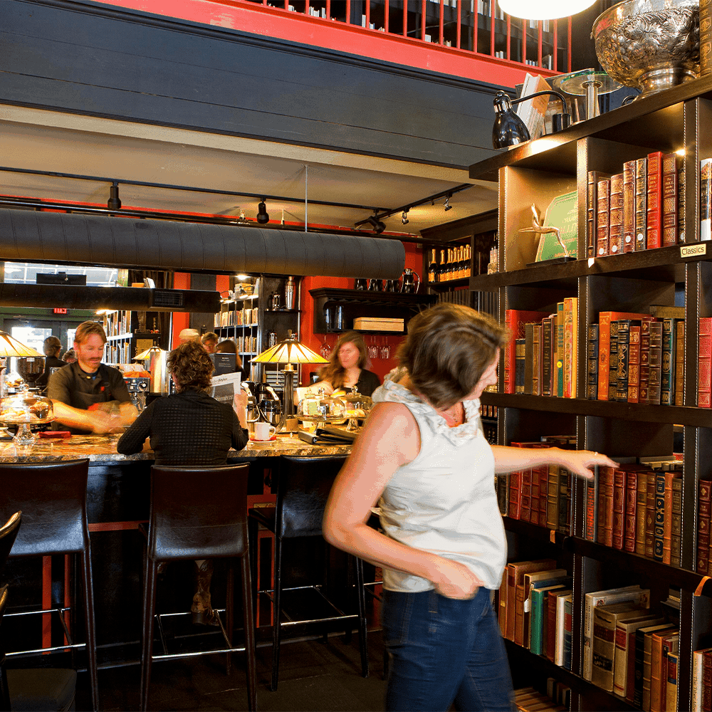 woman browsing for a book by the champagne bar at bpbe