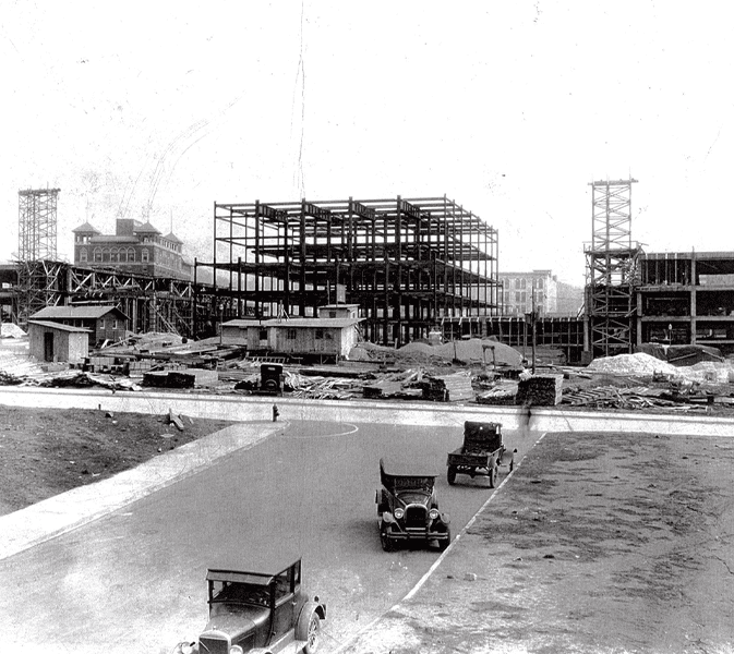 a historic black and white photo of the construction of the Grove Arcade in the 1920s. There are Model T Fords in the foreground