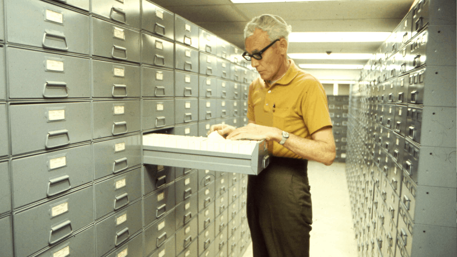 historical photo of man looking through filing cabinets at grove arcade