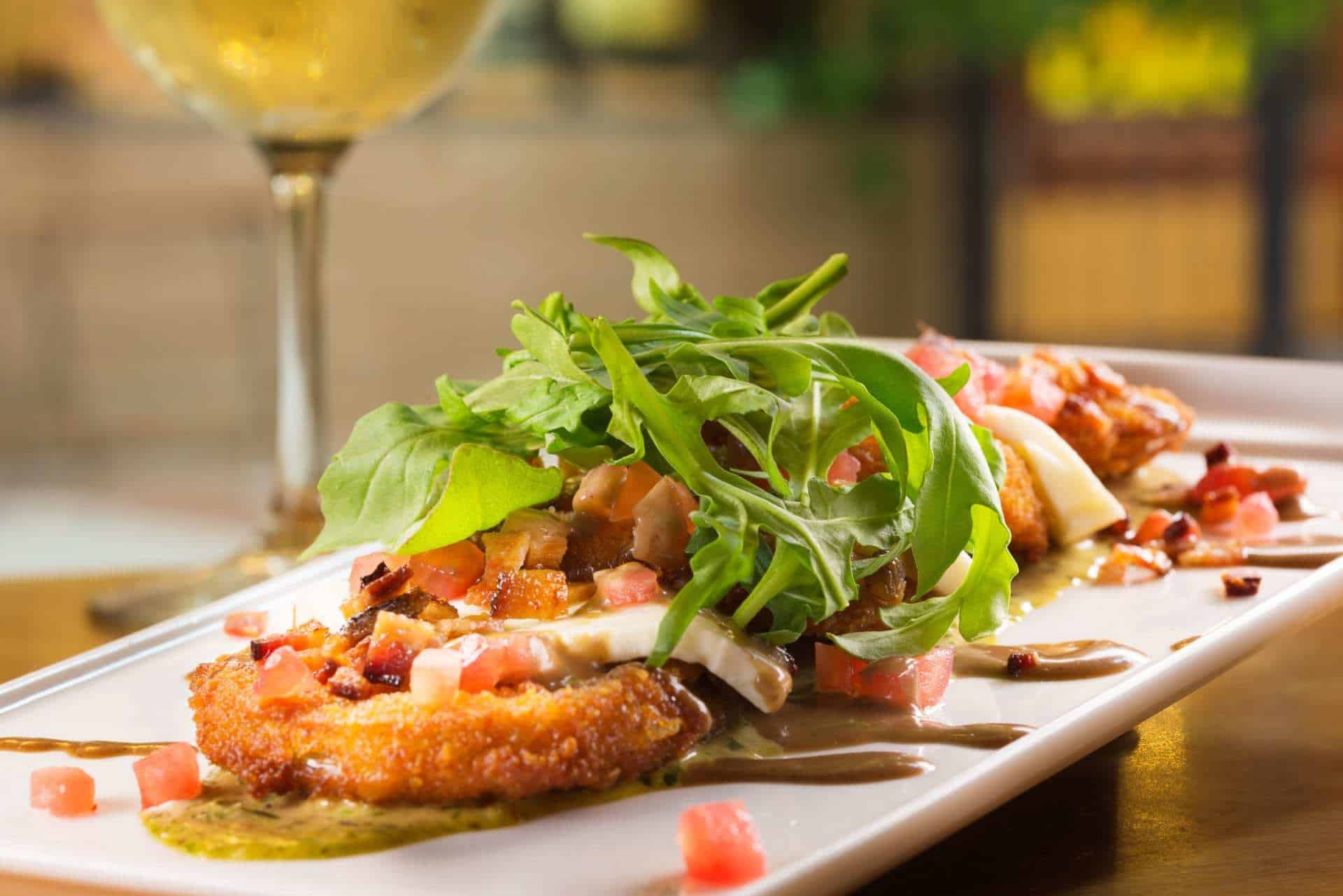 fried green tomatoes with mozzarella, tomatoes, and arugula on a plate