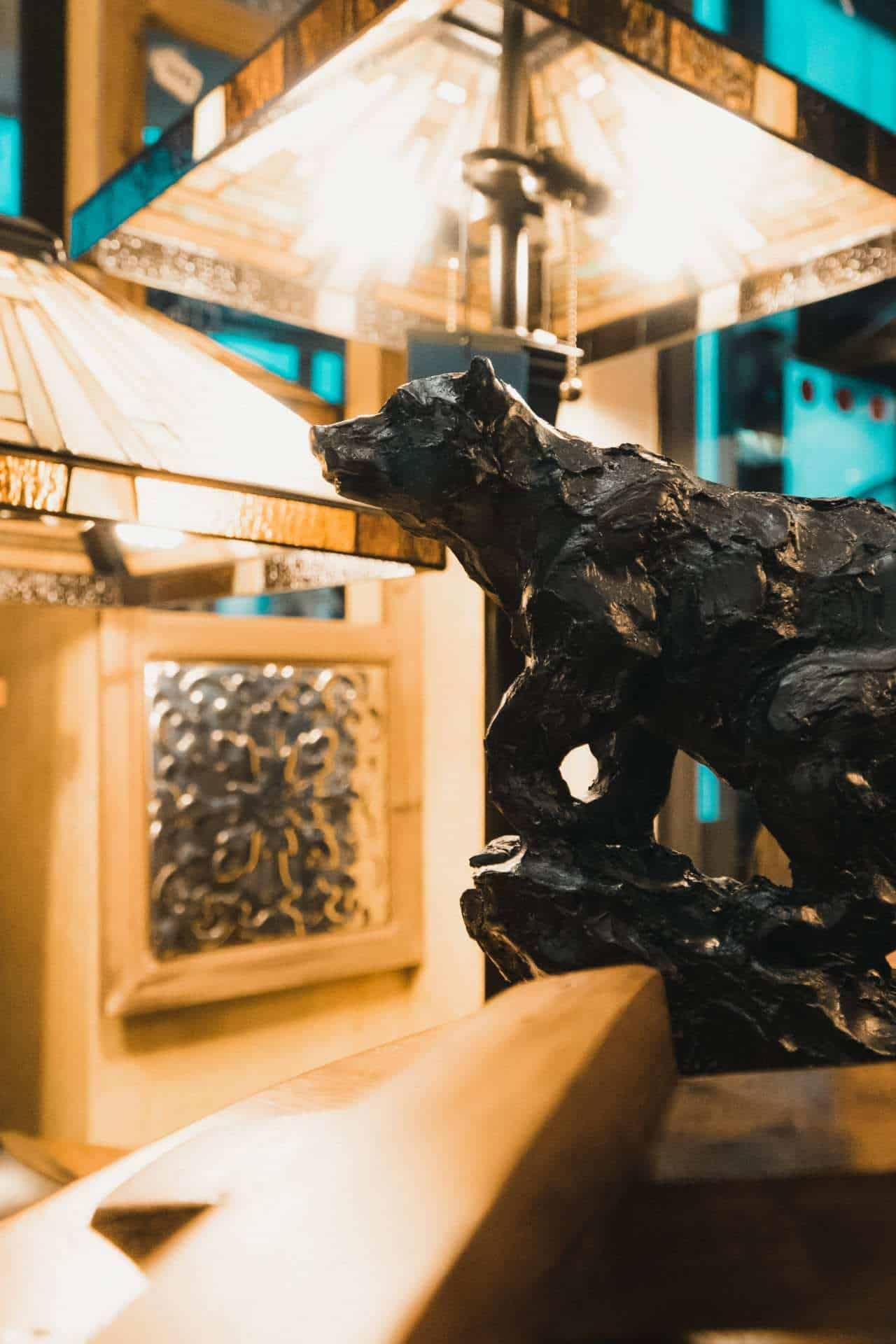 a close up shot of a small sculpture of a black bear and a couple of lamps in the background